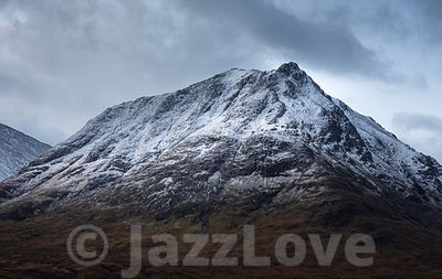 Snowcapped mountain peak in Scottish highlands.