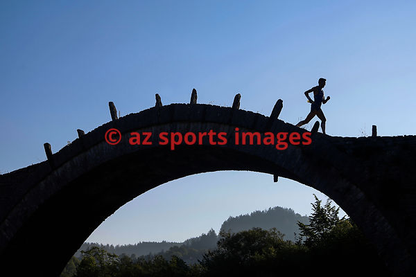 Trail runner crosses the old three arch stone bridge during the 9th Zagori Mountain Running event in Ζagori, Ioannina, Greece...
