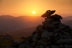 The warm evening sunlight behind a closeup of the mountain summit cairn of Rampsgill Head at sunset in the Lake District UK.