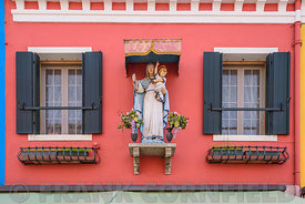 BURANO, ITALY - NOVEMBER 25, 2017: Statue of the Madona with child on a colourful house in Burano, Venice, Italy.