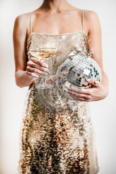 Woman in golden dress holding glass of champagne and discoball