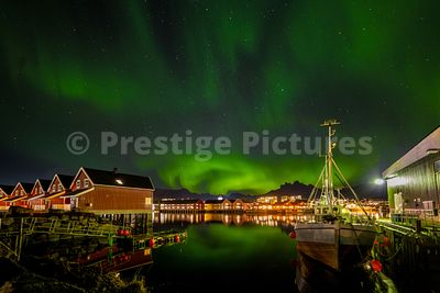 Northern Lights in the sky over typical Norwegian red houses and fishing boat reflecting in the harbour waters in Svolvaer, N...