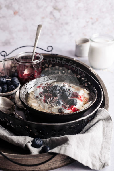 Oatmeal with berries and yogurt in a metal tray