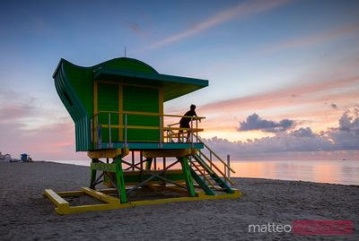 Young man on lifeguard cabin at sunrise, Miami beach, USA