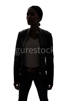 A tough woman, in a leather jacket, in silhouette – shot from eye level.