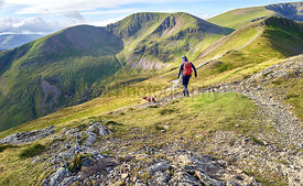 A hiker walking downhill from the summit of Grisedale Pike towards Hobcarton with the summits of Crag Hill an Sail in the dis...