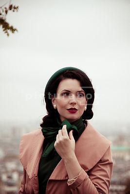 A vintage woman in a hat and coat, looking away.