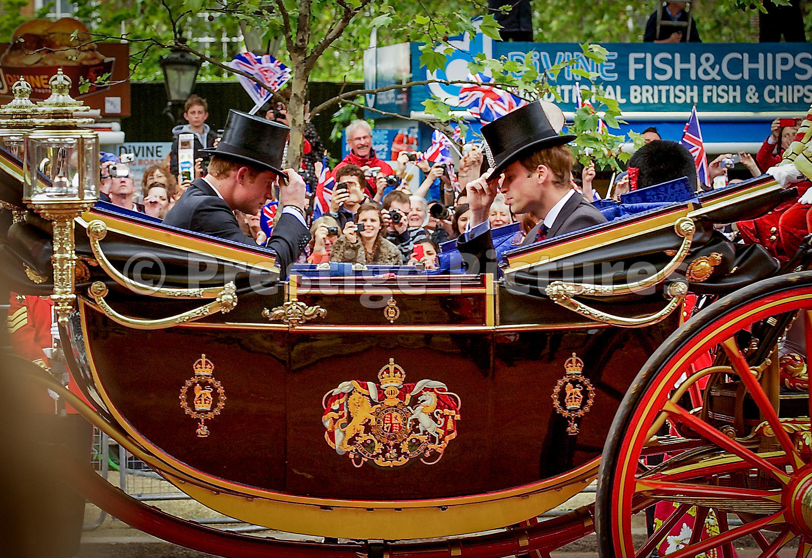Princes William and Harry tipping their ceremonial top hats at one another in an open carriage