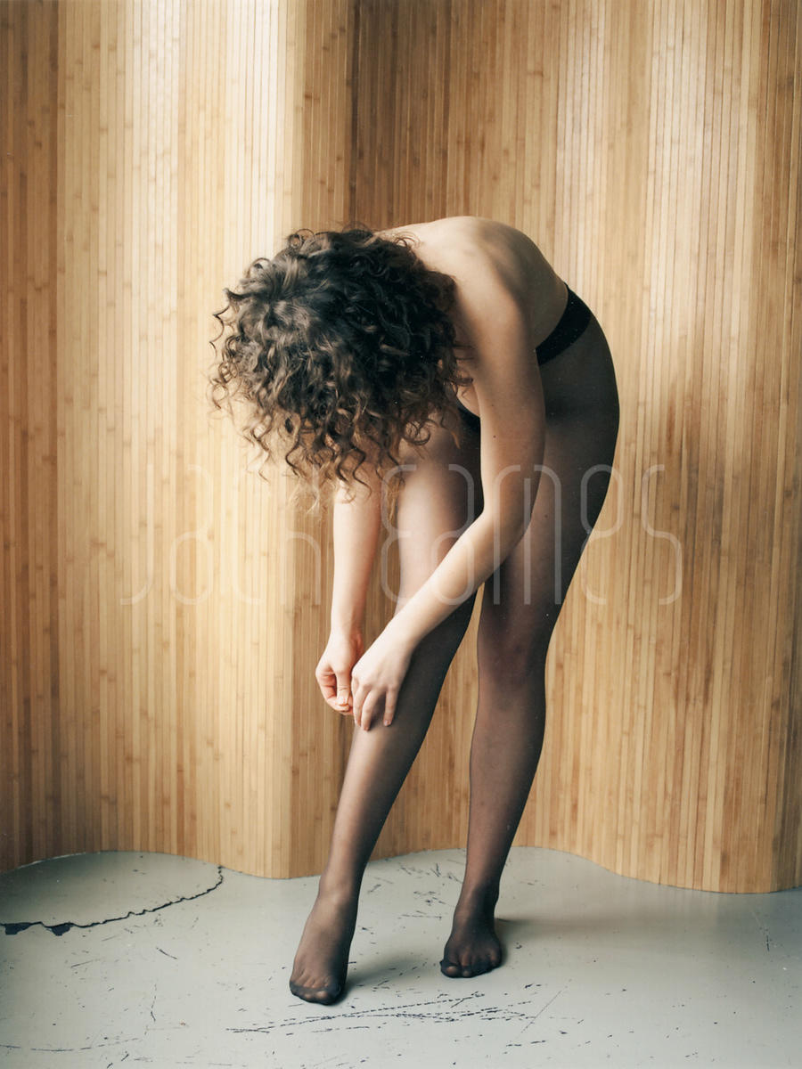 Beautiful Young Topless Brunette Woman With Curly Hair Pulling Up Her Tights