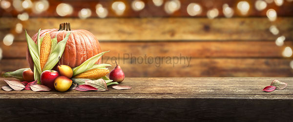 Thanksgiving celebration banner of pumpkins, apples, pears and corncobs on the left hand side of a table with a wooden backgr...