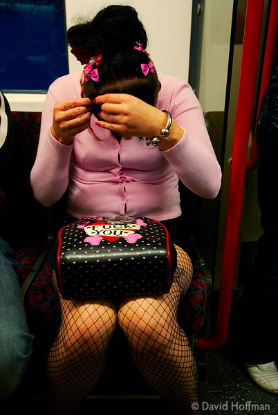 Young woman with handbag adjusting her hair on the tube