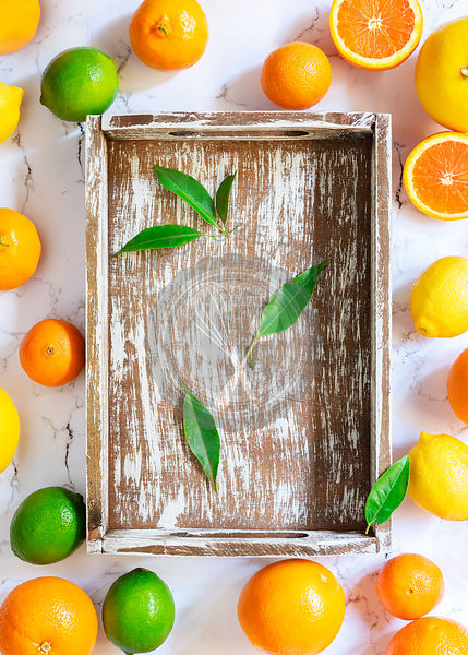 Citrus fruit around an empty wooden tray.