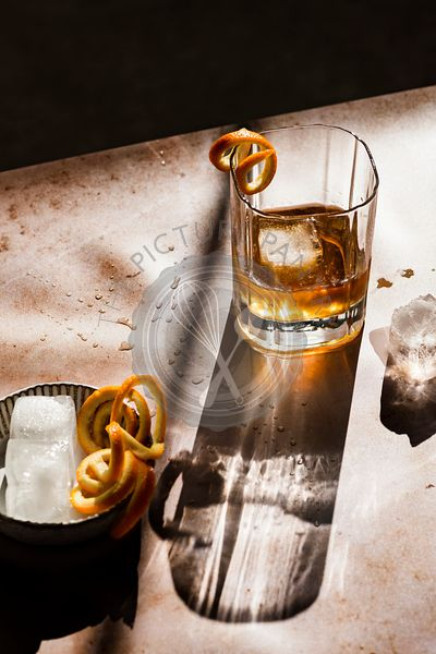Whiskey in hard light with orange spirals next to a small bowl with ice cubes.