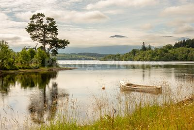 Landscape image of rowing boat and reflections across Loch Lochy, Scotland