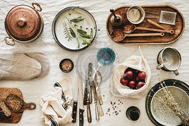 Various kitchen utensils, tablewear and fresh bread over linen tablecloth