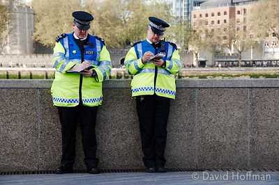 Police make notes during a protest outside City Hall, London.