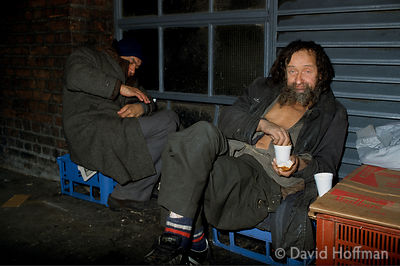 Homeless men with food brought to them by charities sleep on milk crates by hot air vent in newspaper print room, Fleet Stree...