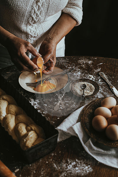 A Woman Prepares Homemade Braided Bread at Home. Close up of Woman Hands and Spilled Egg