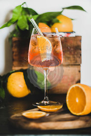 Aperol Spritz cocktail in glass with eco-friendly straw, close-up