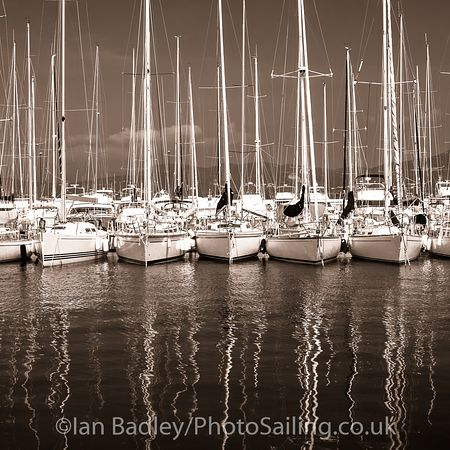 Moored yachts in a south of France marina with reflections. Black and white.