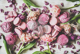 Flat-lay of macaron cookies, marshmallows and flowers over wooden background
