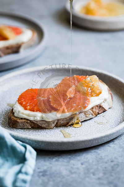 Honey orange ricotta toast on a ceramic plate.