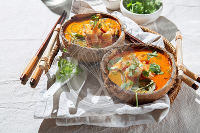 Thai red curry soup with shrimps and coconut milk. Panaeng Curry  in natural coconut plates on gray tablecloth