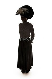 A Silhouette of an Edwardian woman in a big hat, standing – shot from eye-level.