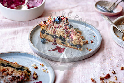 Closeup view of gluten-free blueberry coffee cake with pecan streusel on a plate.