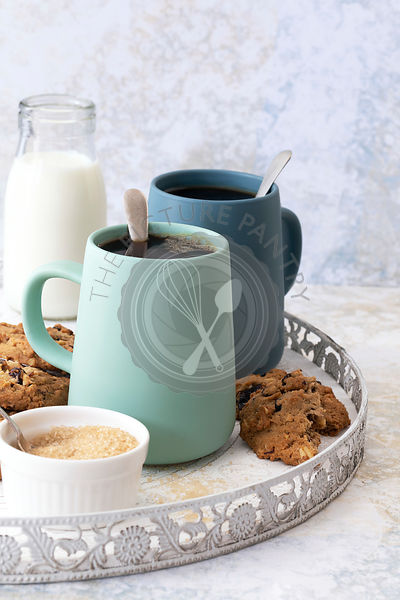 Mugs of black coffee on a serving tray with milk, sugar and sultana cookies.
