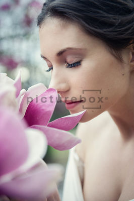 An atmospheric image af a woman in a white dress, smelling a flower, in a country garden.