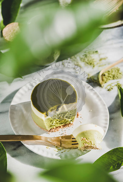 Green matcha cheesecake over grey marble background, top view