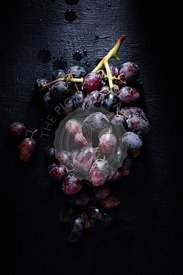 A bunch of dark red grapes on a black background