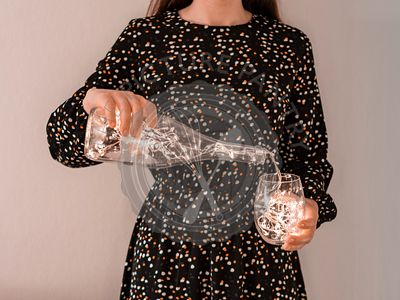 woman pouring glowing garland from wine bottle in glass