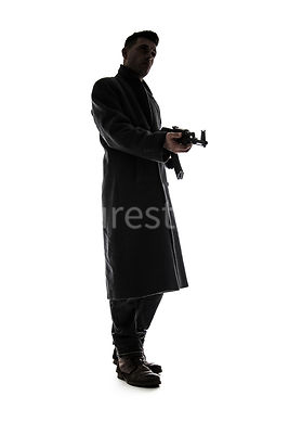 A silhouette of a mystery man, in a long coat, holding an AK-47 – shot from low level.