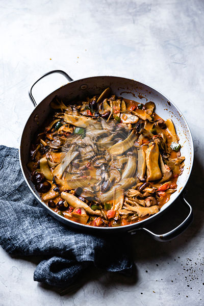 Sliced mushrooms and peppers sauteed in a pan.