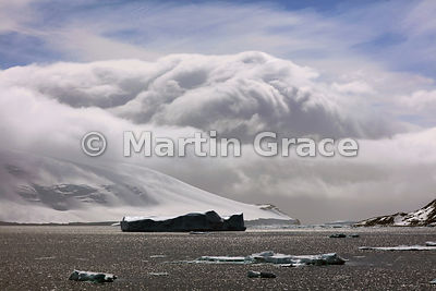 Weddell Sea landscape of icebergs, ice, land, sea and spectacular cloud, Antarctic Peninsula,  Antarctica