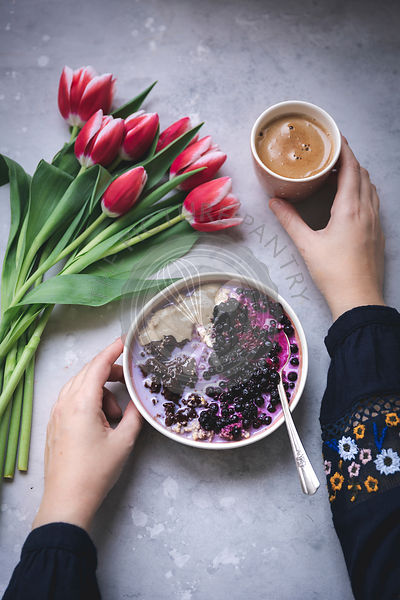 Woman having a bowl of porridge topped with melted chocolate, tahini and blueberries for breakfast