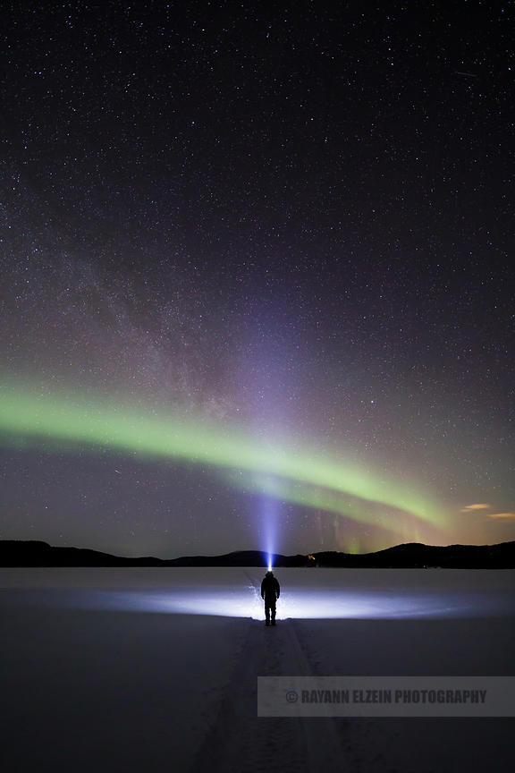 Man standing under the aurora borealis on a frozen lake near Inari in Finnish Lapland