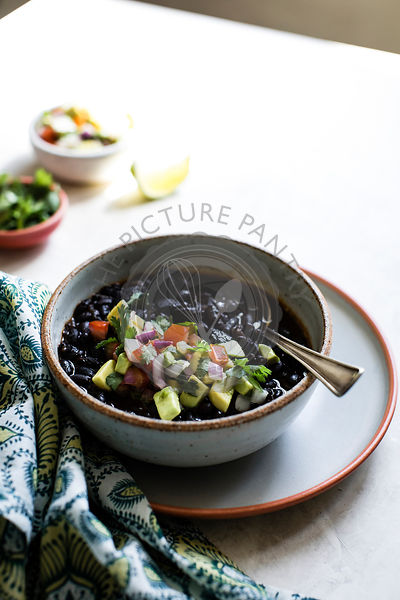 Black beans with avocado, tomato, red onion and cilantro in a ceramic bowl.