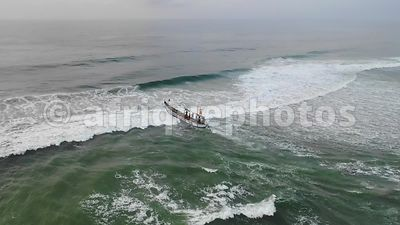 Fishing boat going through waves, Assinie, Ivory Coast