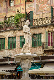 Fountain statue of Madonna and Lamberti tower with clocks on Erbe Square in the medieval city of Verona city, Italy. Torre
