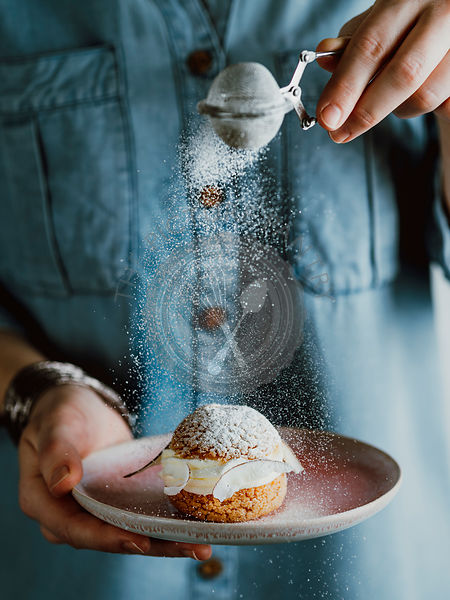 Woman sprinkles icing sugar on Choux cake with fresh berries