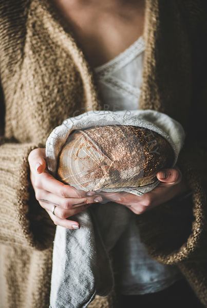 Woman holding healthy wheat Swedish bread round loaf in hands