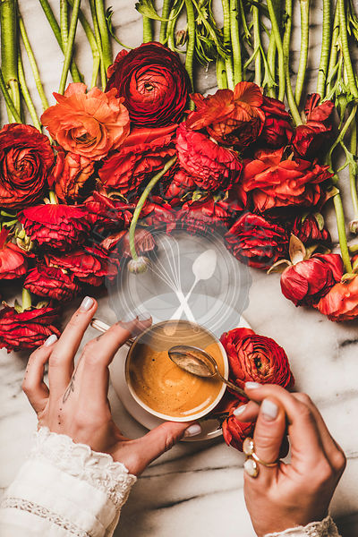 Womans hand holding cup of black coffee over red flowers
