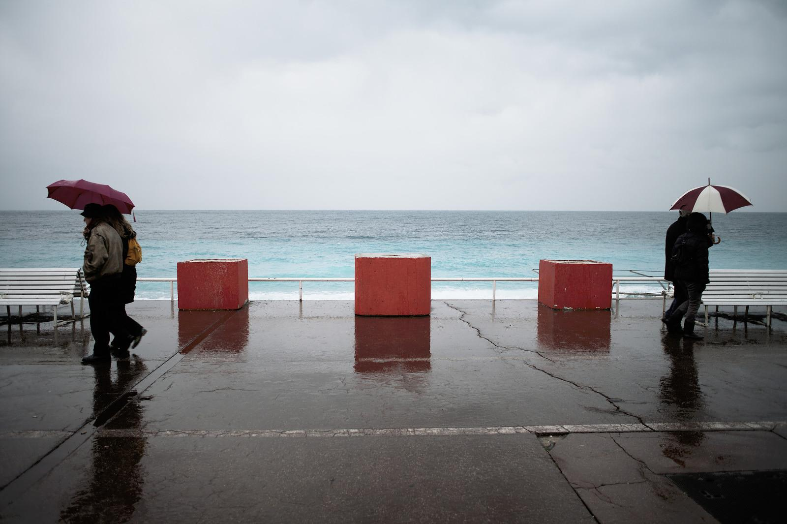 People on an afternoon walk on a rainy afternoon on the Promenade des anglais.