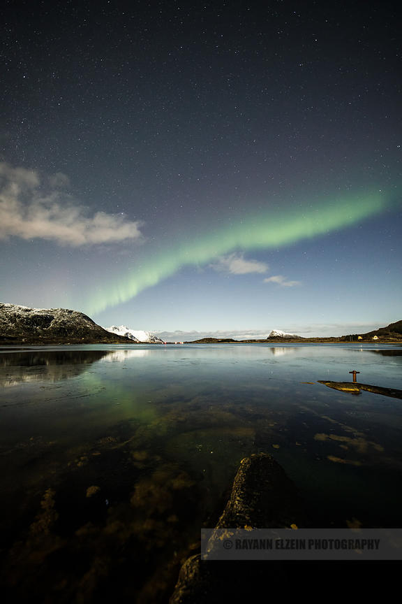 Faint northern lights above a quiet fjord in the Lofoten Islands, Norway