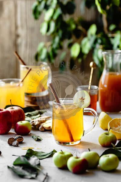 Hot apple cider in glass mugs in bright sunlight