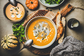 Flat-lay of pumpkin soup with seeds, fresh parsley and cream