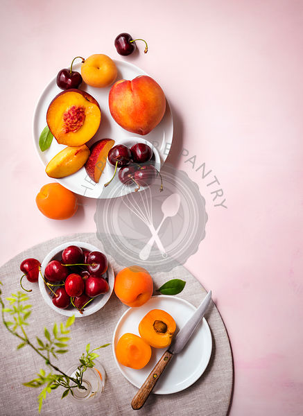 Table setting with summer fruits (nectarines, peaches, cherries and apricots). White plates on a pale pink tabletop. Bright a...